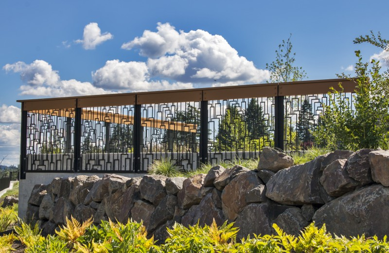 Heavy Duty Cascade Pattern Metal Railing on Rock Wall with Blue Sky Background