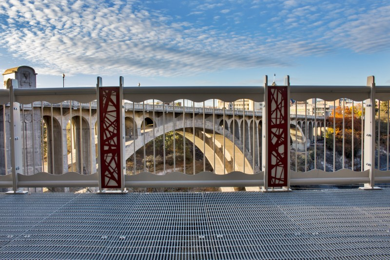Red Nest Pattern Railing Accent Panels With 20th Century Concrete Bridge in Background