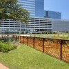 Corten Rusted Metal Railing in Grassy Landscape Area with Cityscape in Background